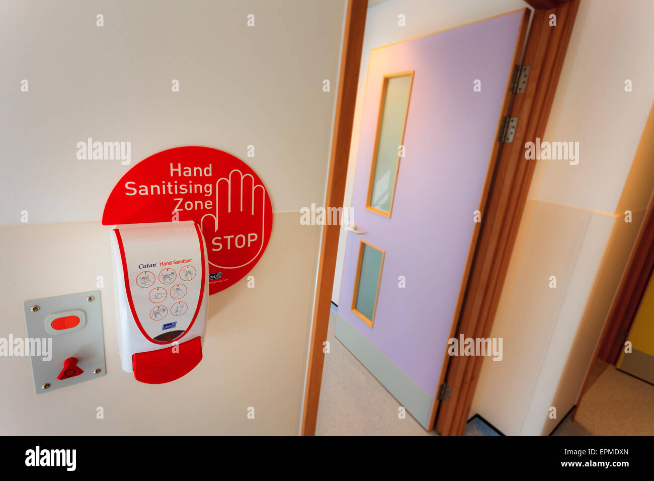 Hand sanitiser station by hospital doorway with hand sanitising zone sign - Stock Image