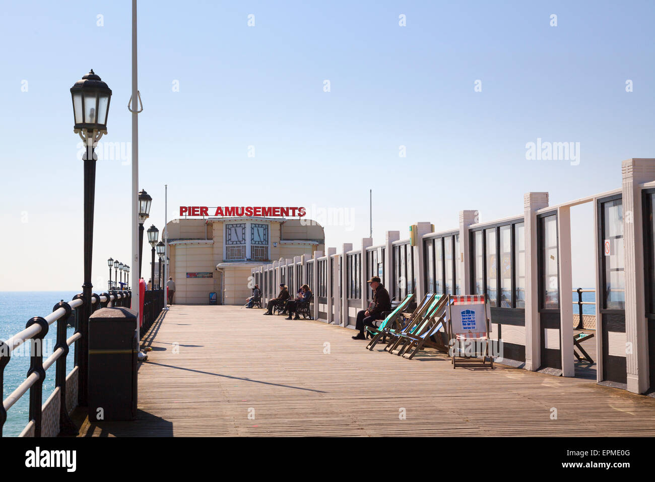 People sitting on Worthing Pier behind glass windbreaks and Pier Amusements sign - Stock Image