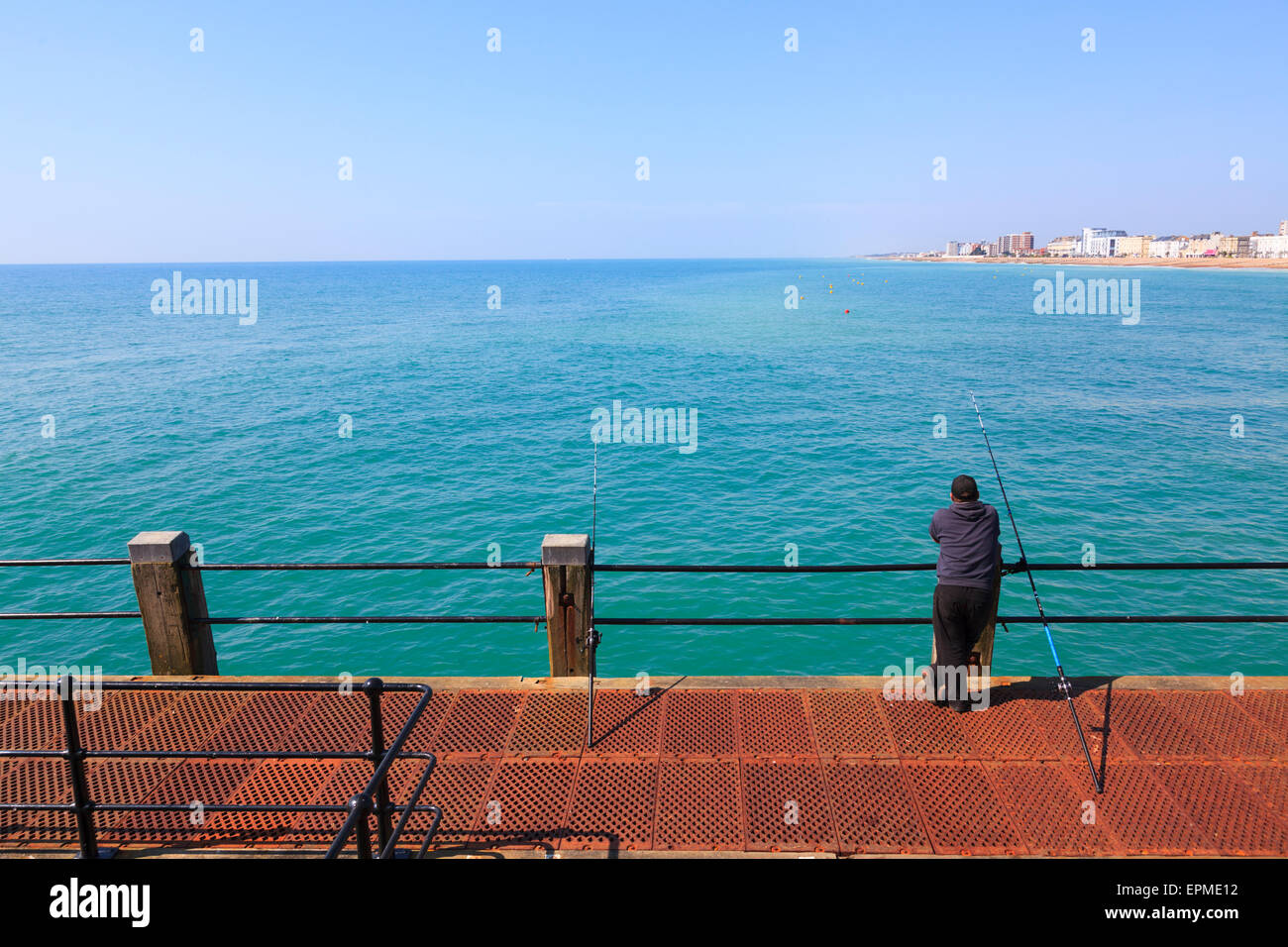 Man casually leaning on railings of Worthing Pier fishing - Stock Image