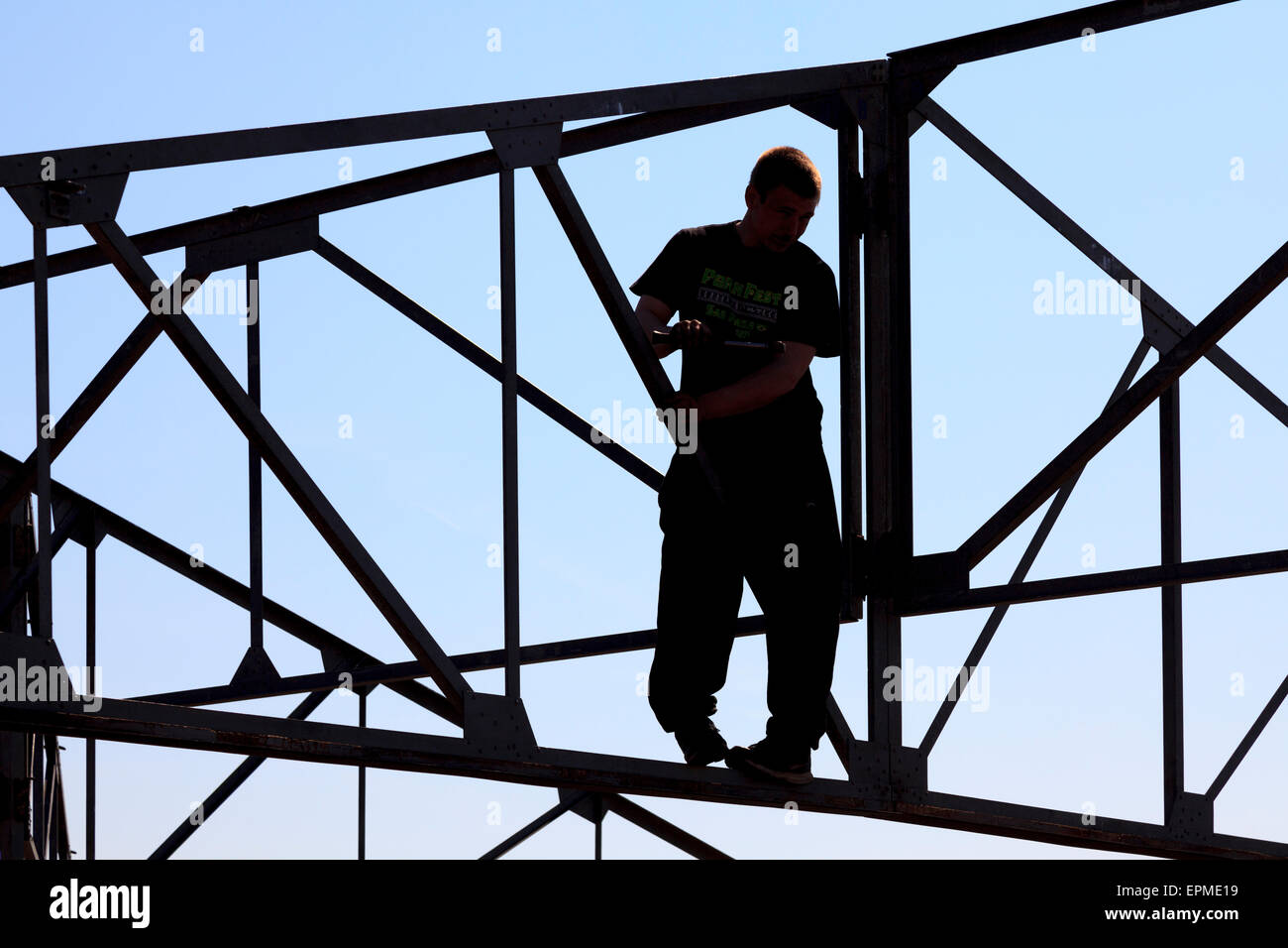 Rigger working amongst steel framework without safety equipment - Stock Image