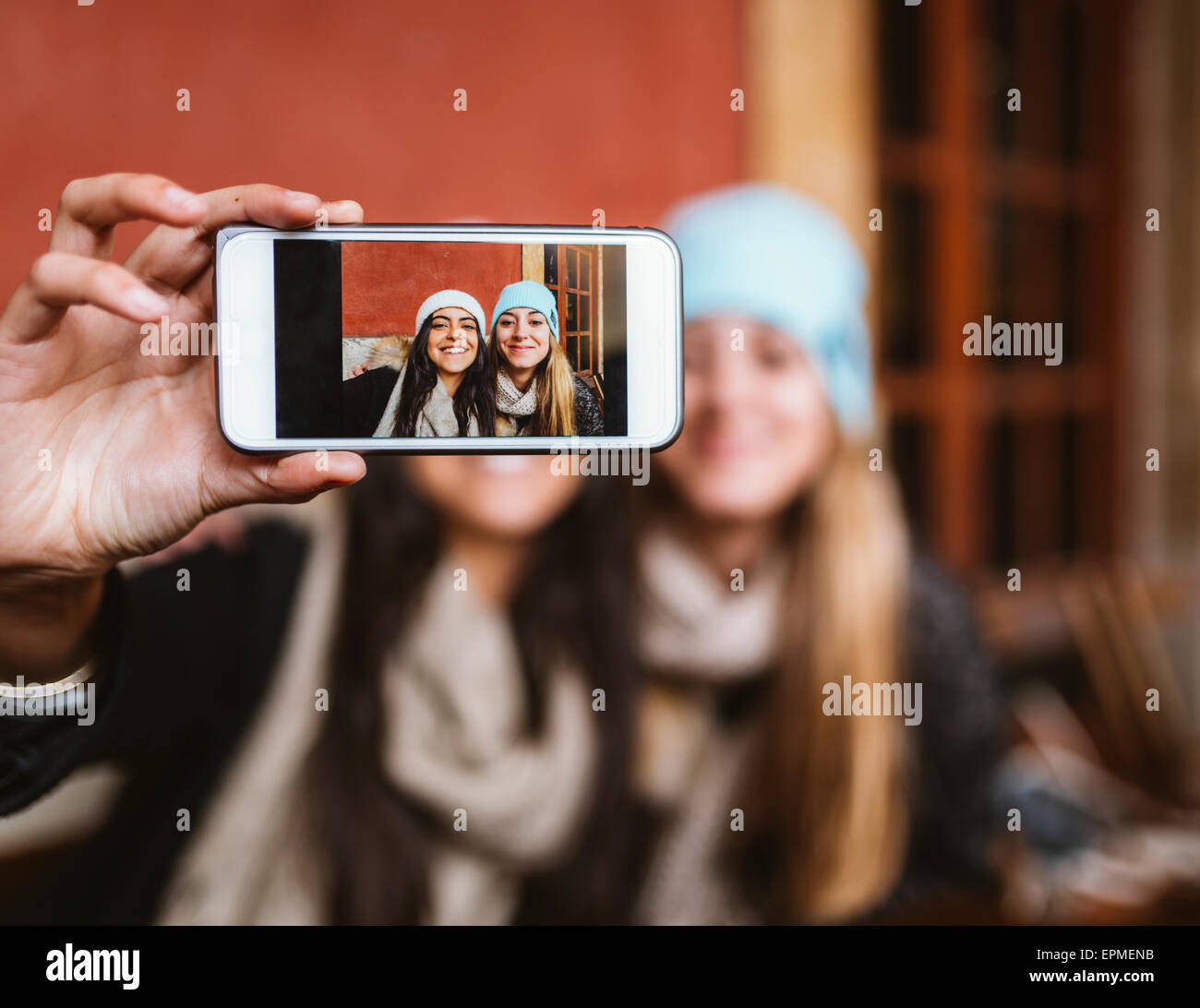 Selfie of two female friends on display of smartphone - Stock Image