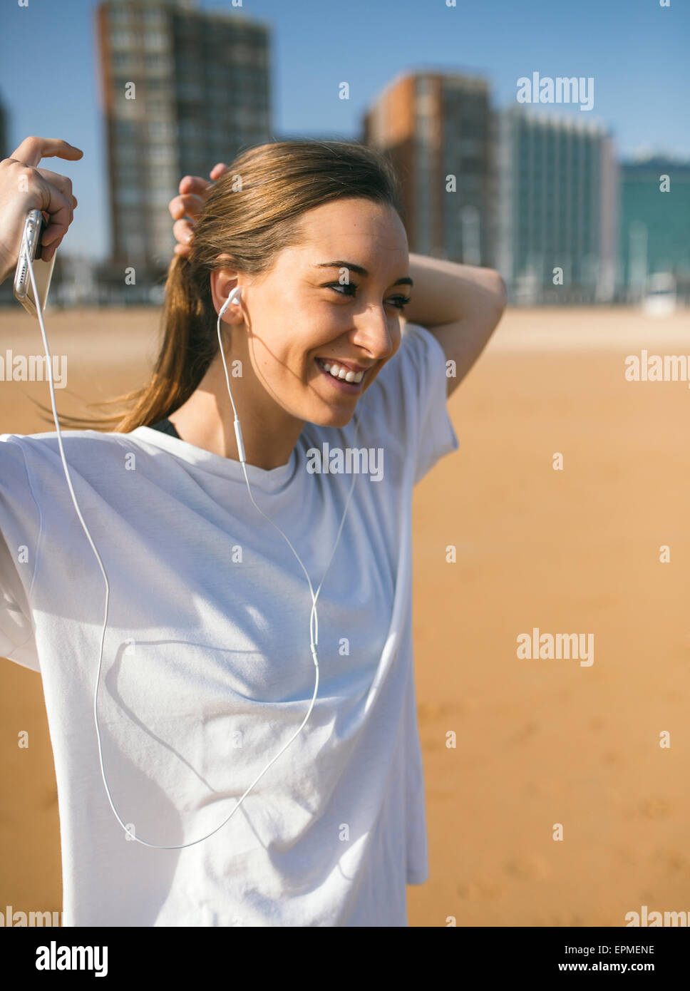 Spain, Gijon, sportive young woman with earbuds on the beach - Stock Image