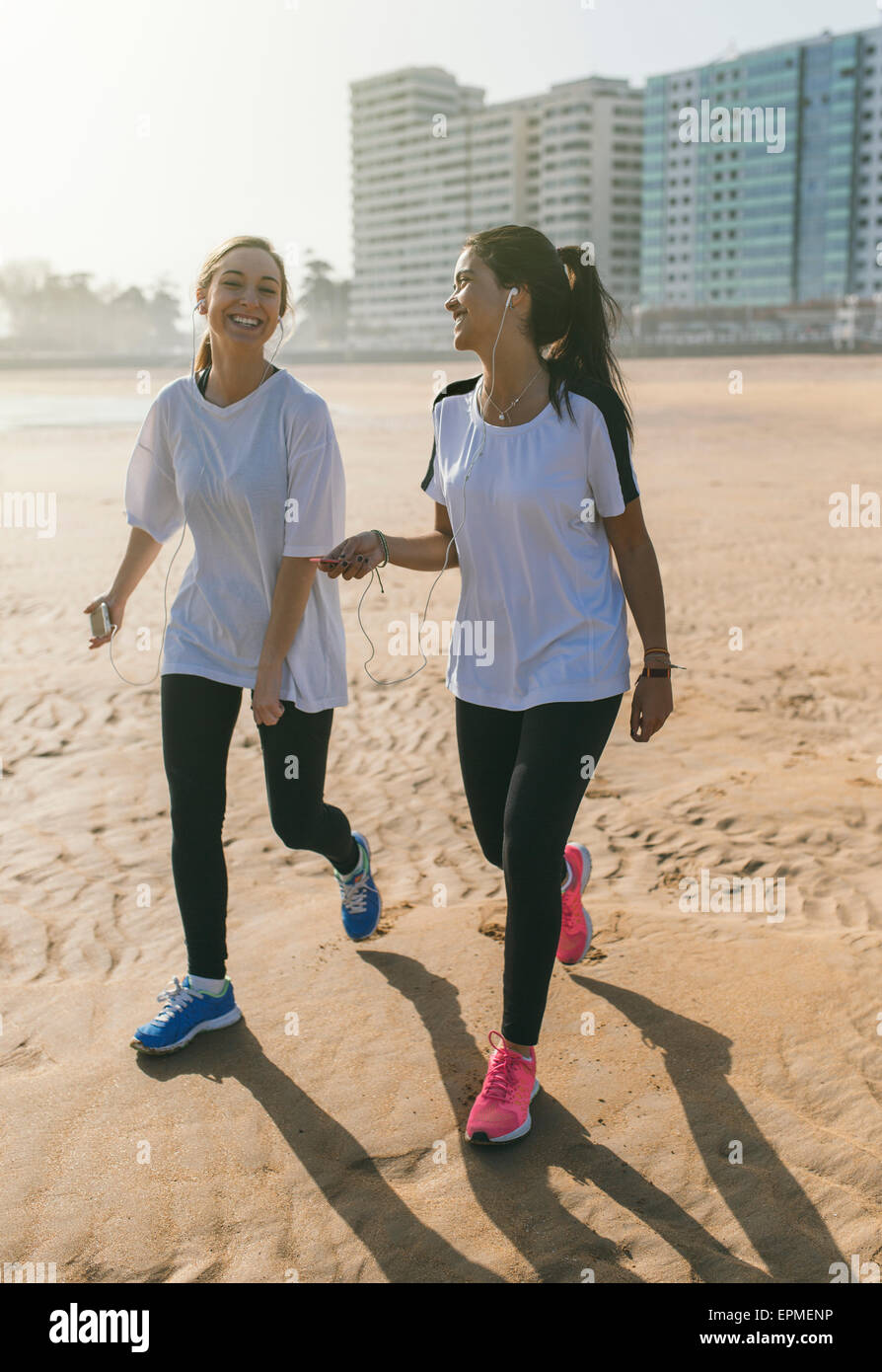 Spain, Gijon, two sportive young women with earbuds walking on the beach - Stock Image
