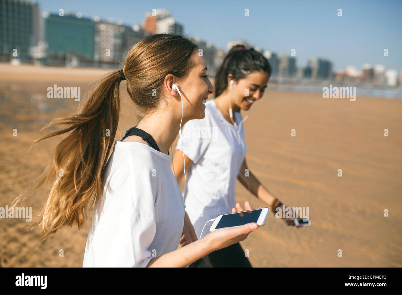 Spain, Gijon, two sportive young women with earbuds on the beach - Stock Image