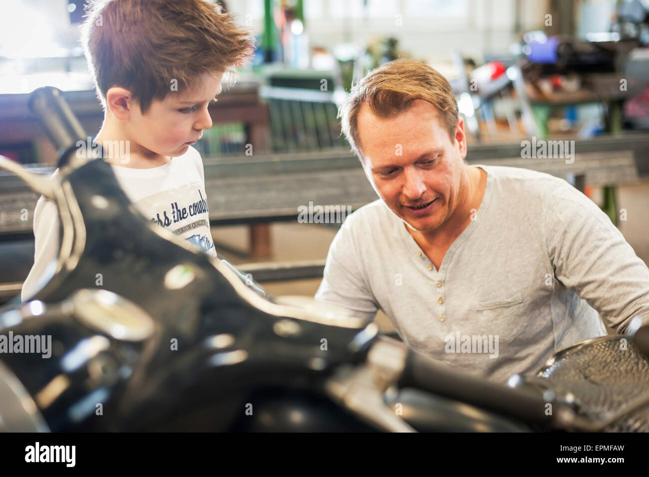Father and son maintaining vintage moped - Stock Image