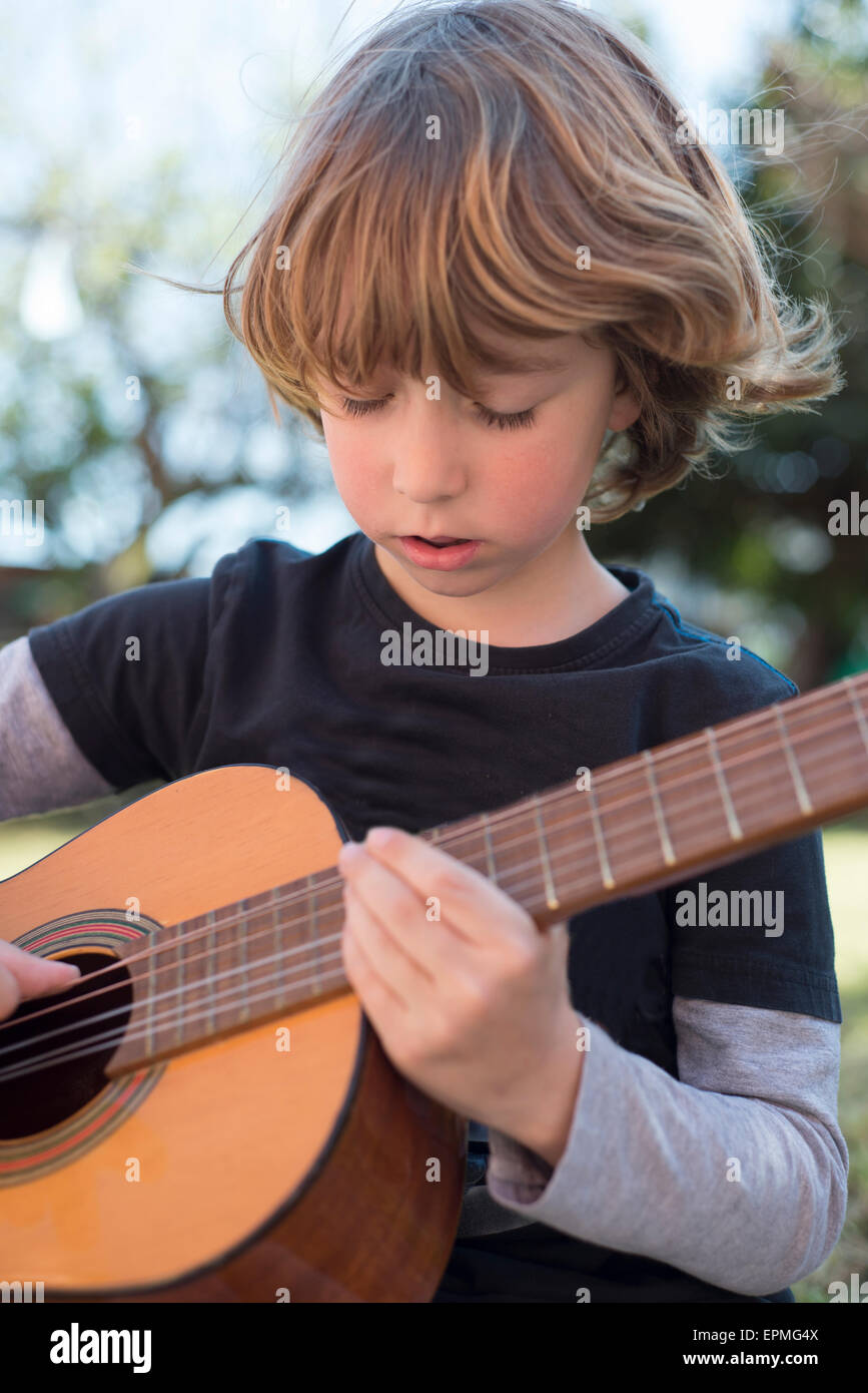 Little boy playing acoustic guitar Stock Photo