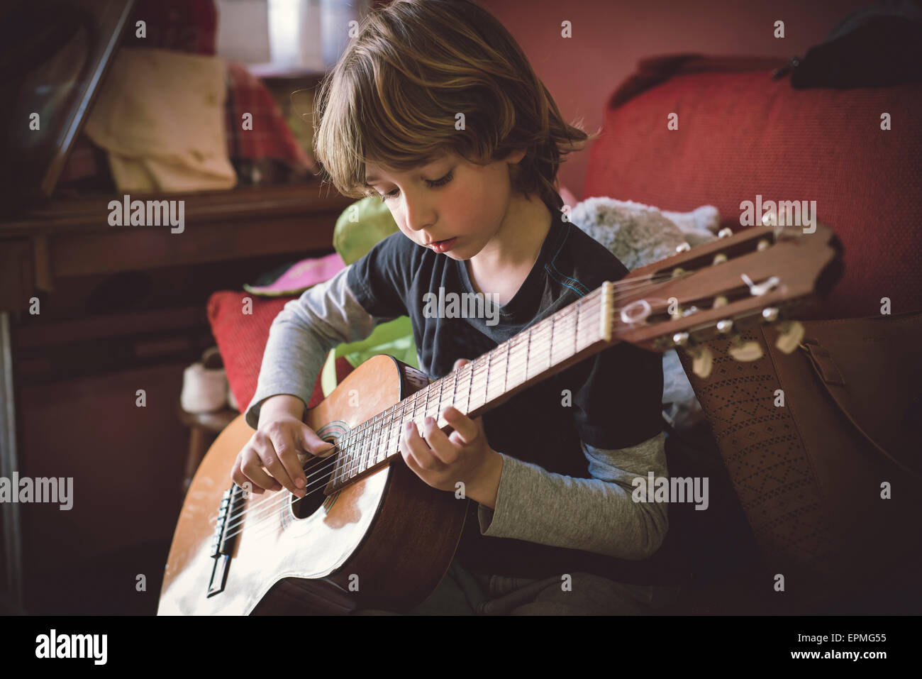 Portrait of little boy playing acoustic guitar at home Stock Photo