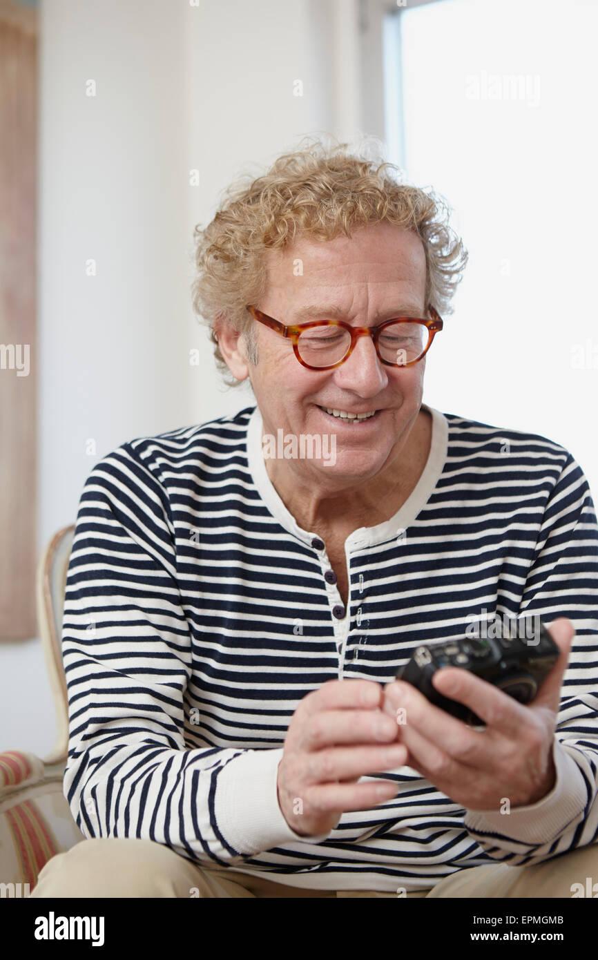 Senior man holding analogue camera - Stock Image