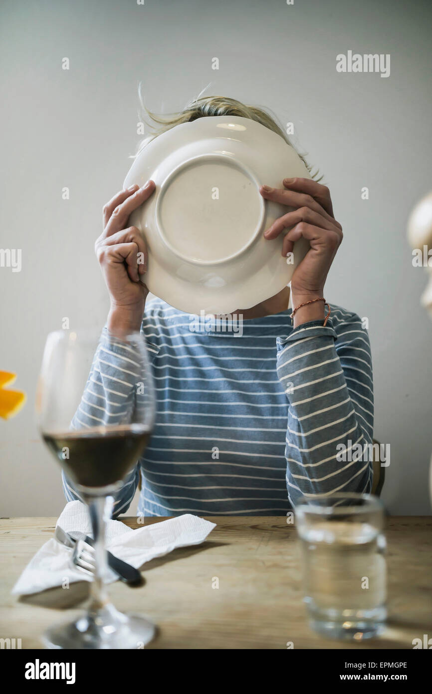 Woman licking off a plate at home - Stock Image