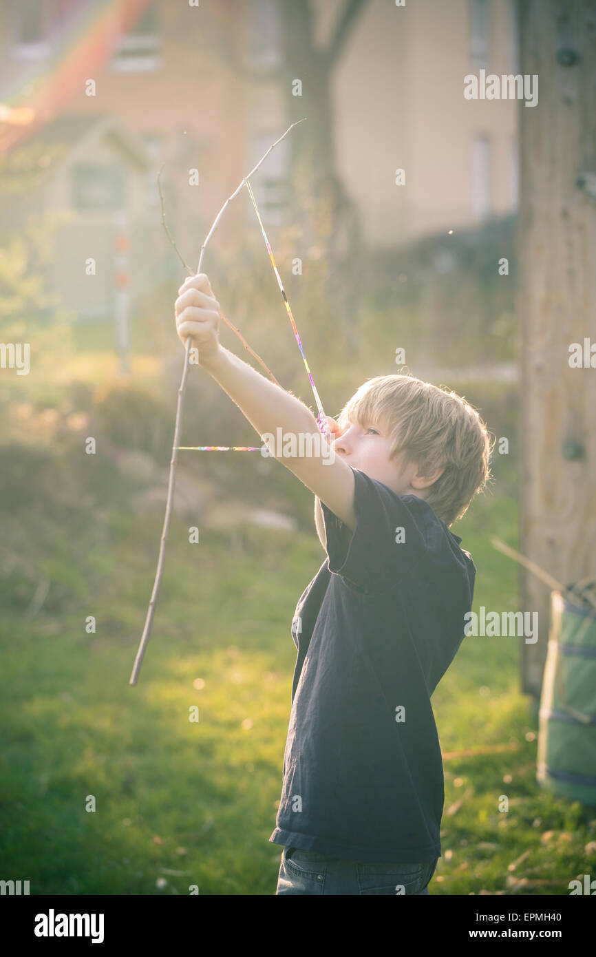 Boy using bow self-built of twigs and looms - Stock Image