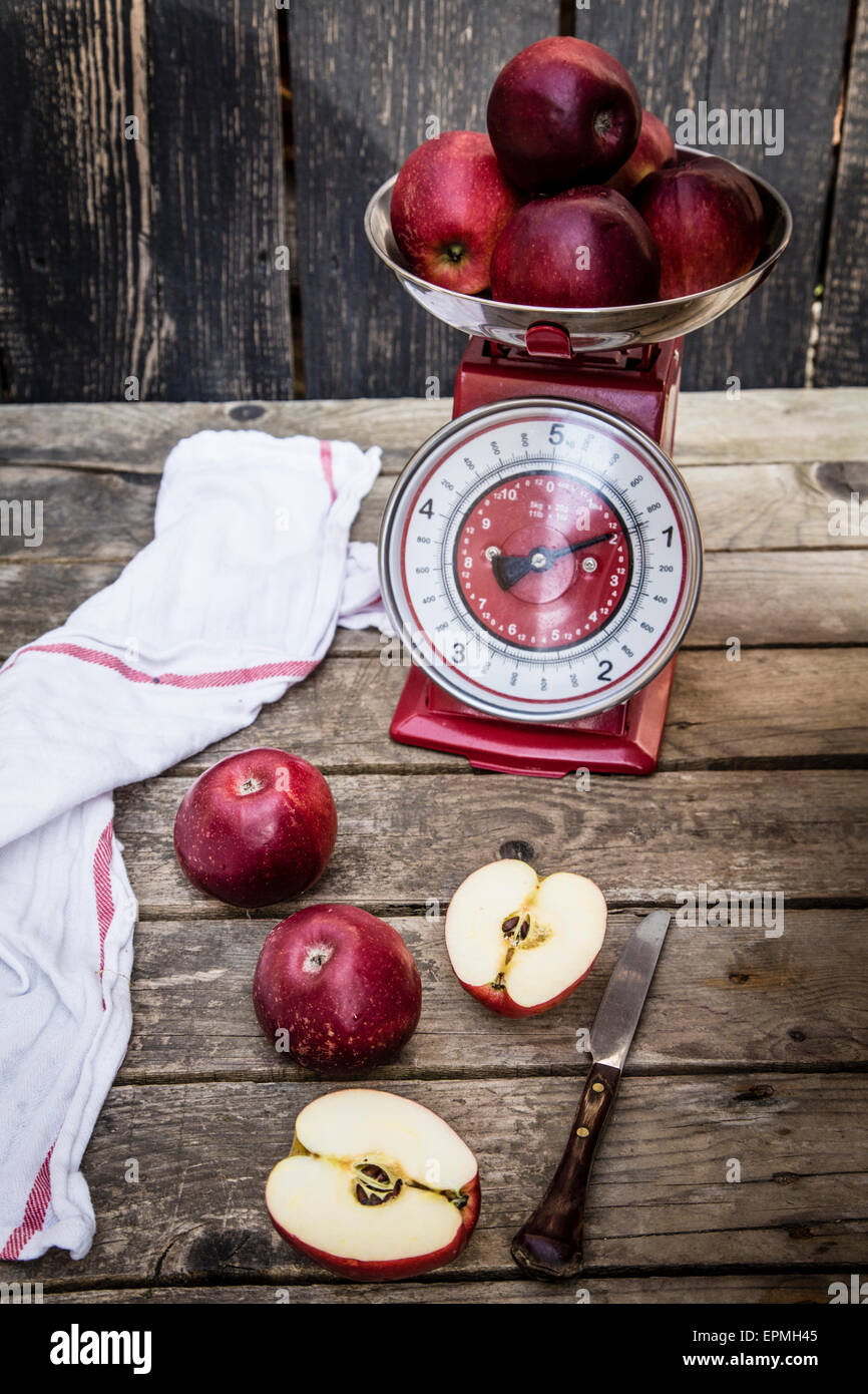 Red apples, scale and knife on dark wood - Stock Image