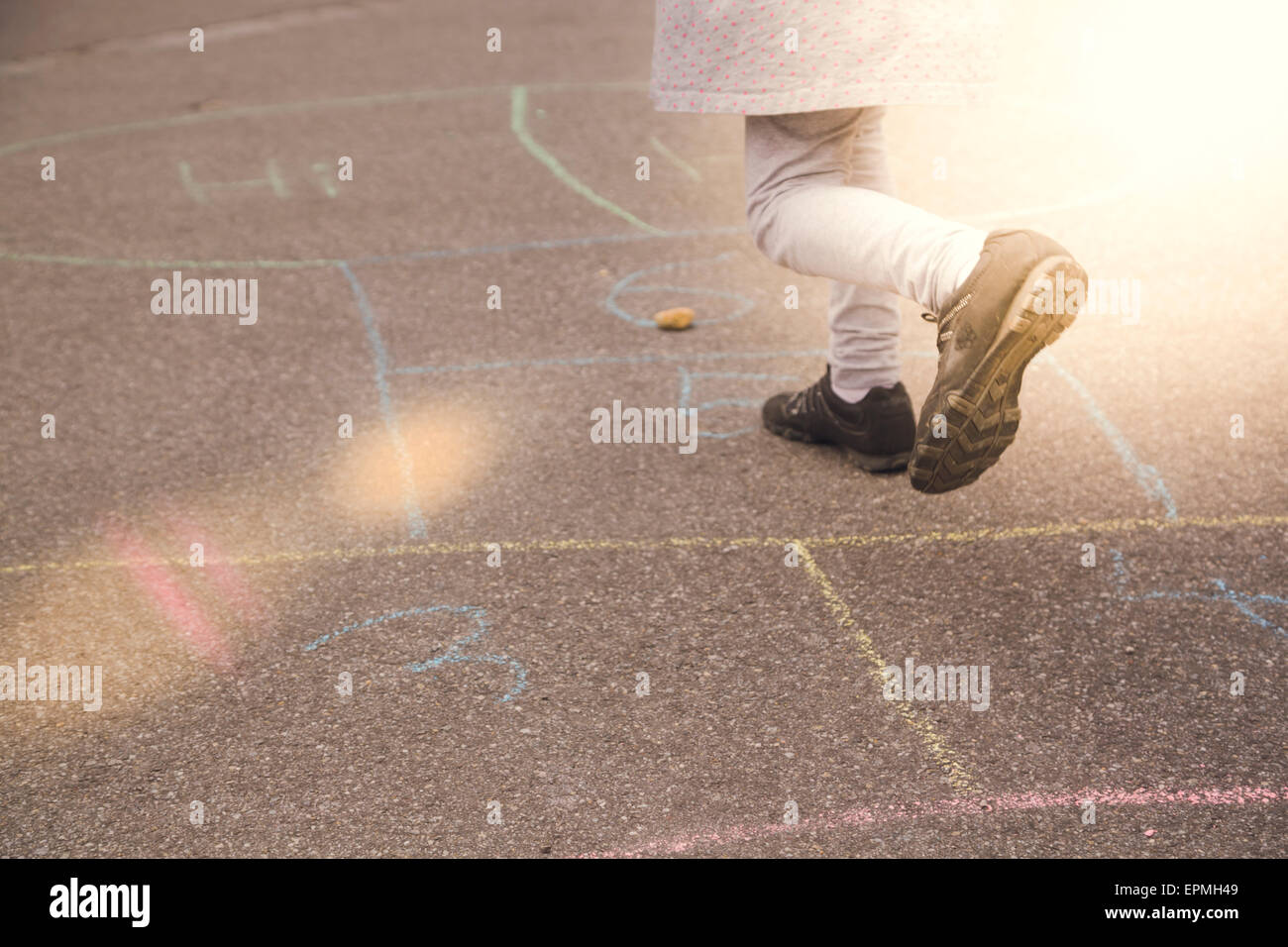 Little girl playing hopscotch Stock Photo