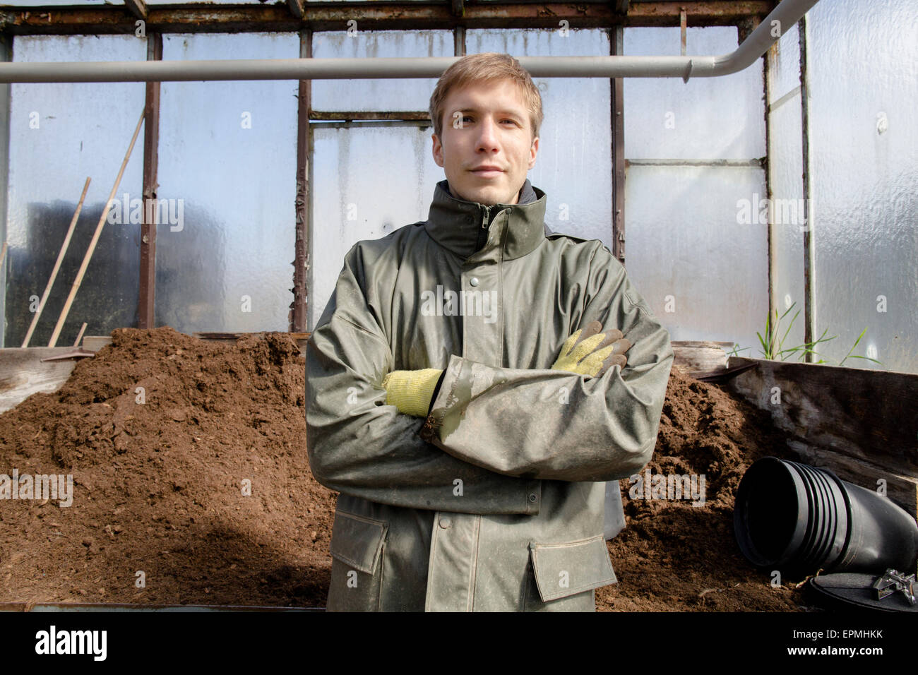 Young gardener at work, filling mother soil - Stock Image