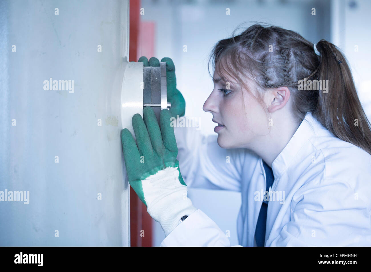 Young woman in lab coat looking through peephole - Stock Image