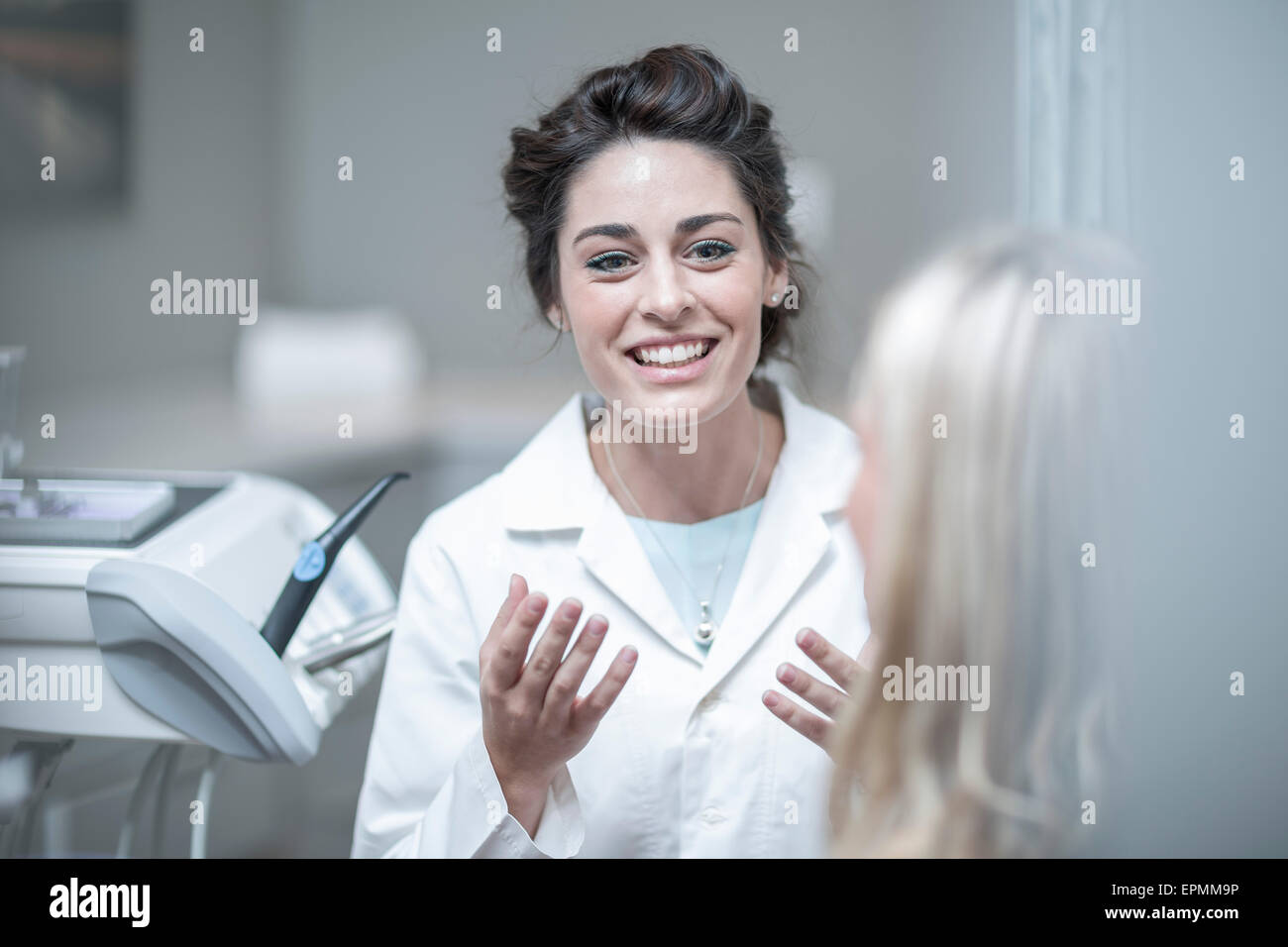 Dentist explaining procedure to patient sitting in dentist's chair - Stock Image