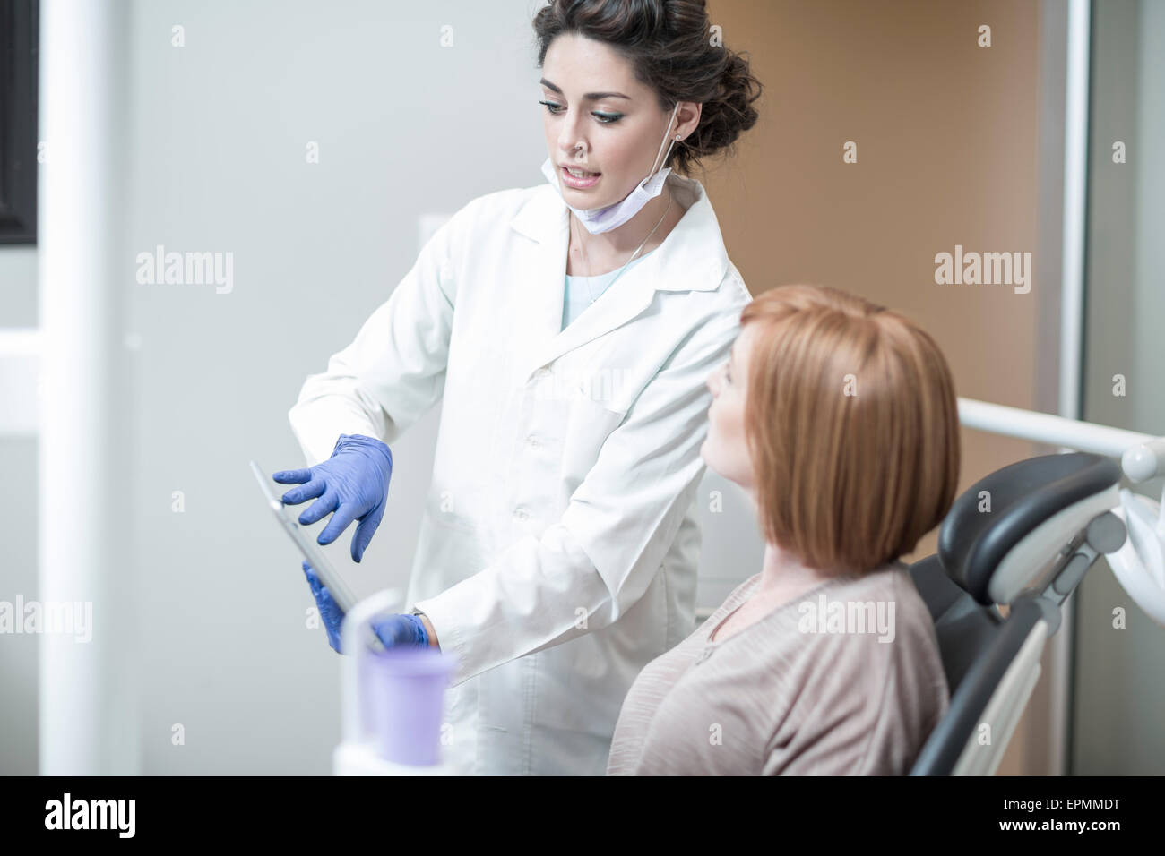 Dentist explaining a procedure and results with a patient - Stock Image