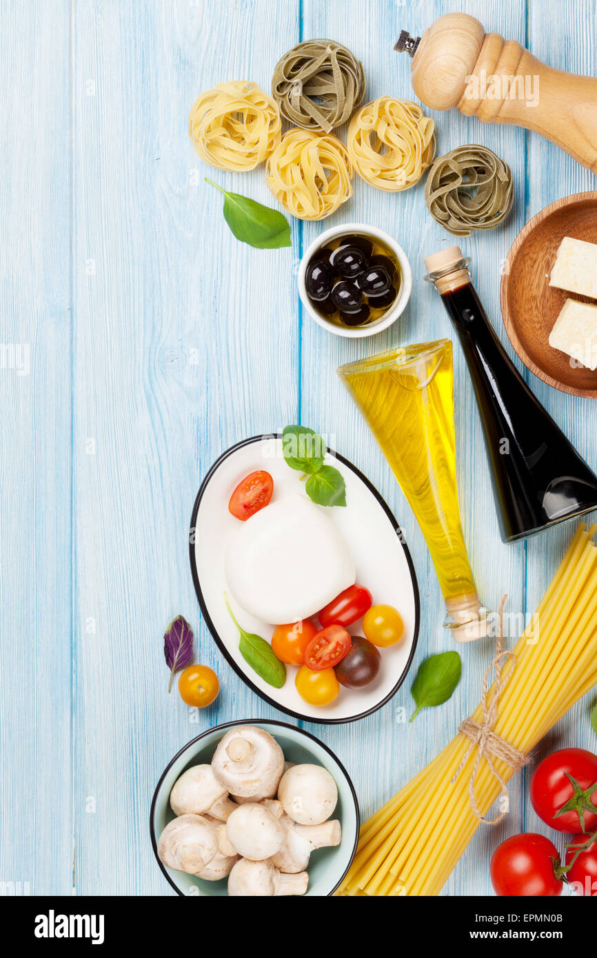Mozzarella, tomatoes, basil and olive oil on wooden table. Top view with copy space Stock Photo