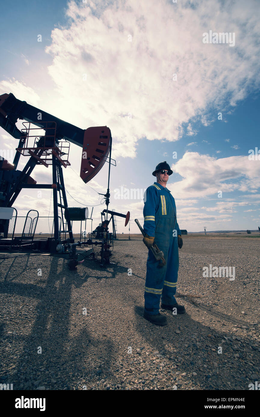 A man in overalls and hard hat at a pump jack in open ground at an oil extraction site. - Stock Image