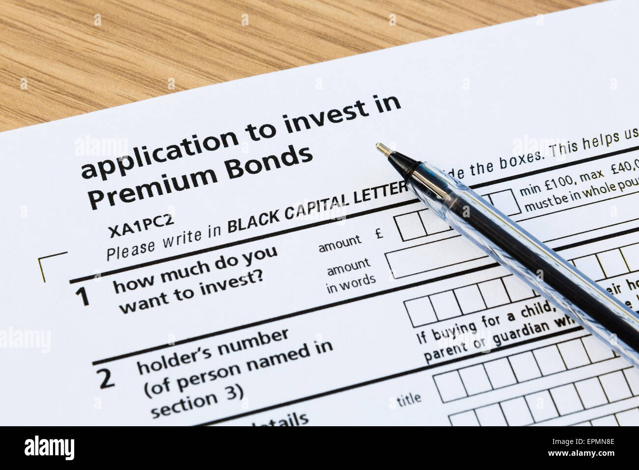Application form to invest in Premium Bonds and a black ballpoint pen for completing the investment paperwork.  - Stock Image
