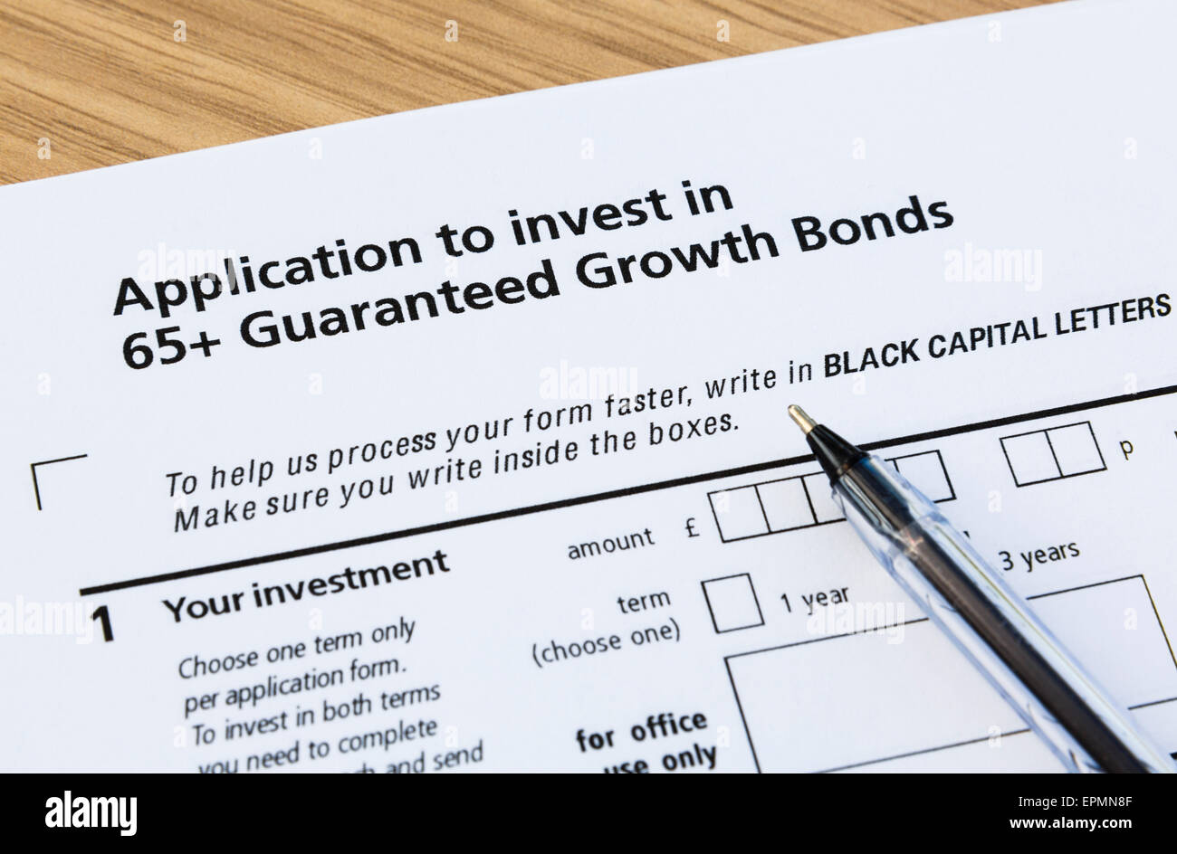 Application form to buy pensioners' 65+ Guaranteed Growth Bonds and a black ballpoint pen for completing. England - Stock Image