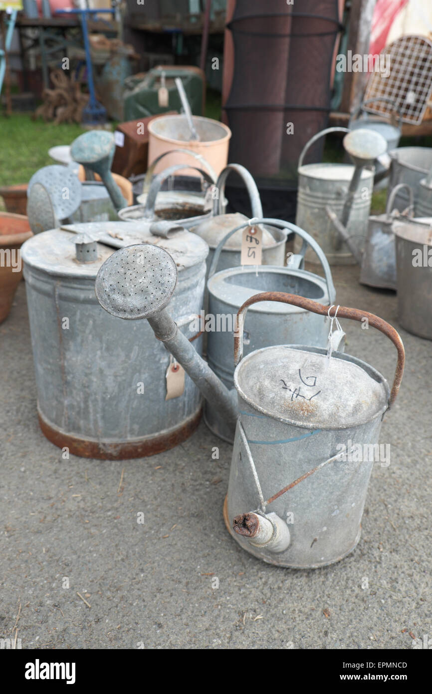 Old galvanised metal watering cans for sale at a secondhand reclamation centre - Stock Image