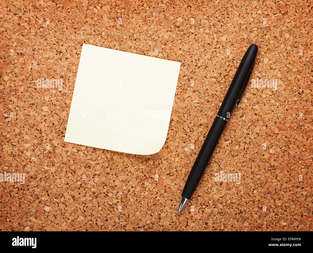 Blank postit note on cork notice board with pen - Stock Image