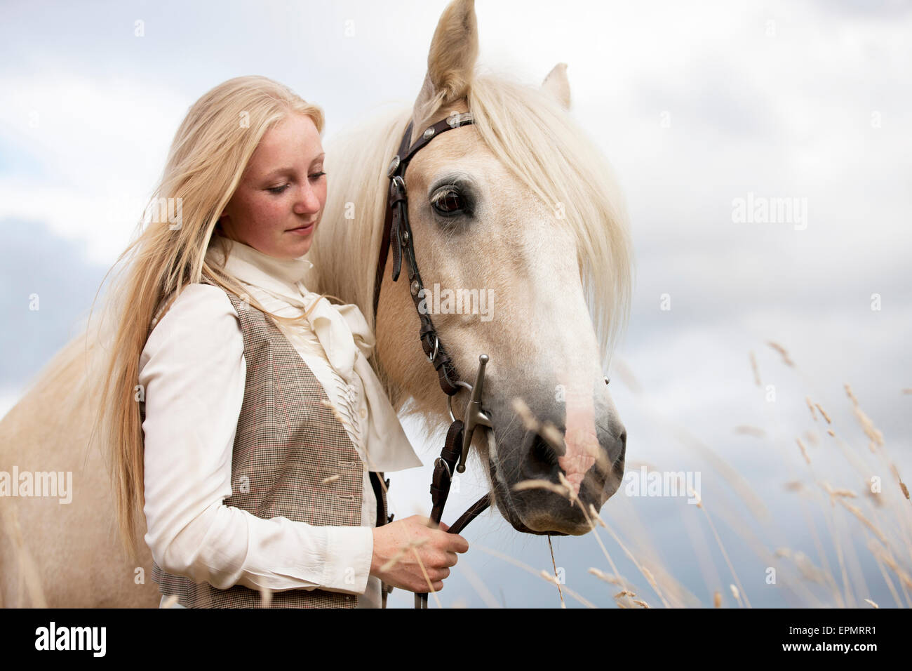 A young woman standing with a palomino horse - Stock Image