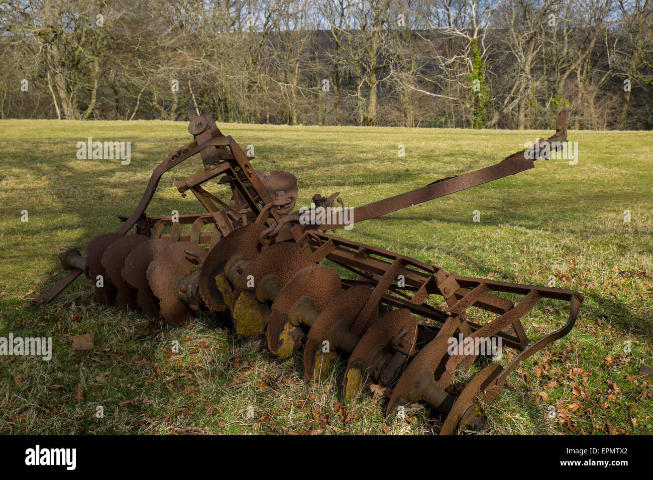 Vintage rusty agricultural machinery equipment in field near Pentyrch, Cardiff, South Glamorgan, South Wales, uk - Stock Image