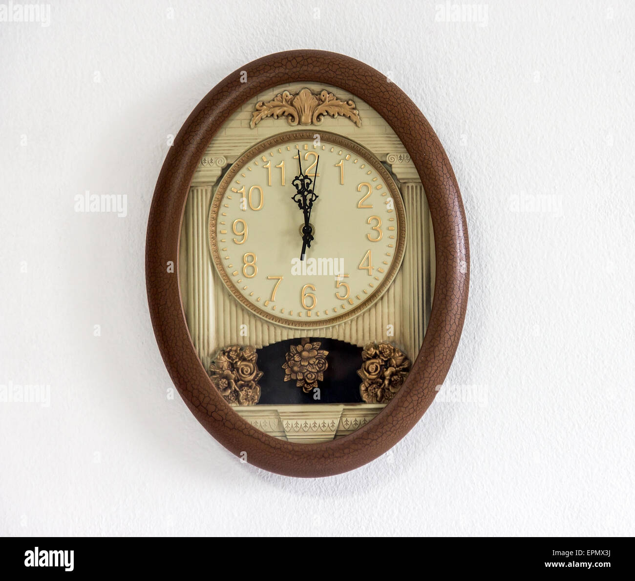 clock with pendulum hanging at the white wall showing twelve o'clock - Stock Image