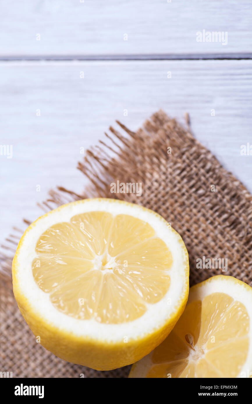 Lemon cut in half and sat on hessian material - Stock Image