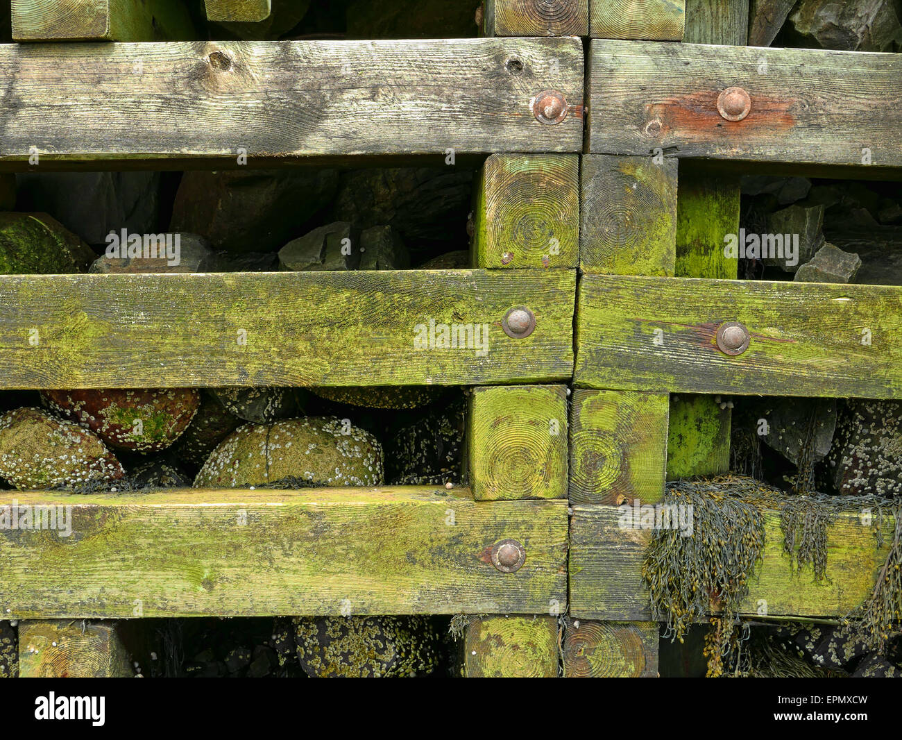 View of a post and beam rock filled retaining wall for a pier at low tide. - Stock Image