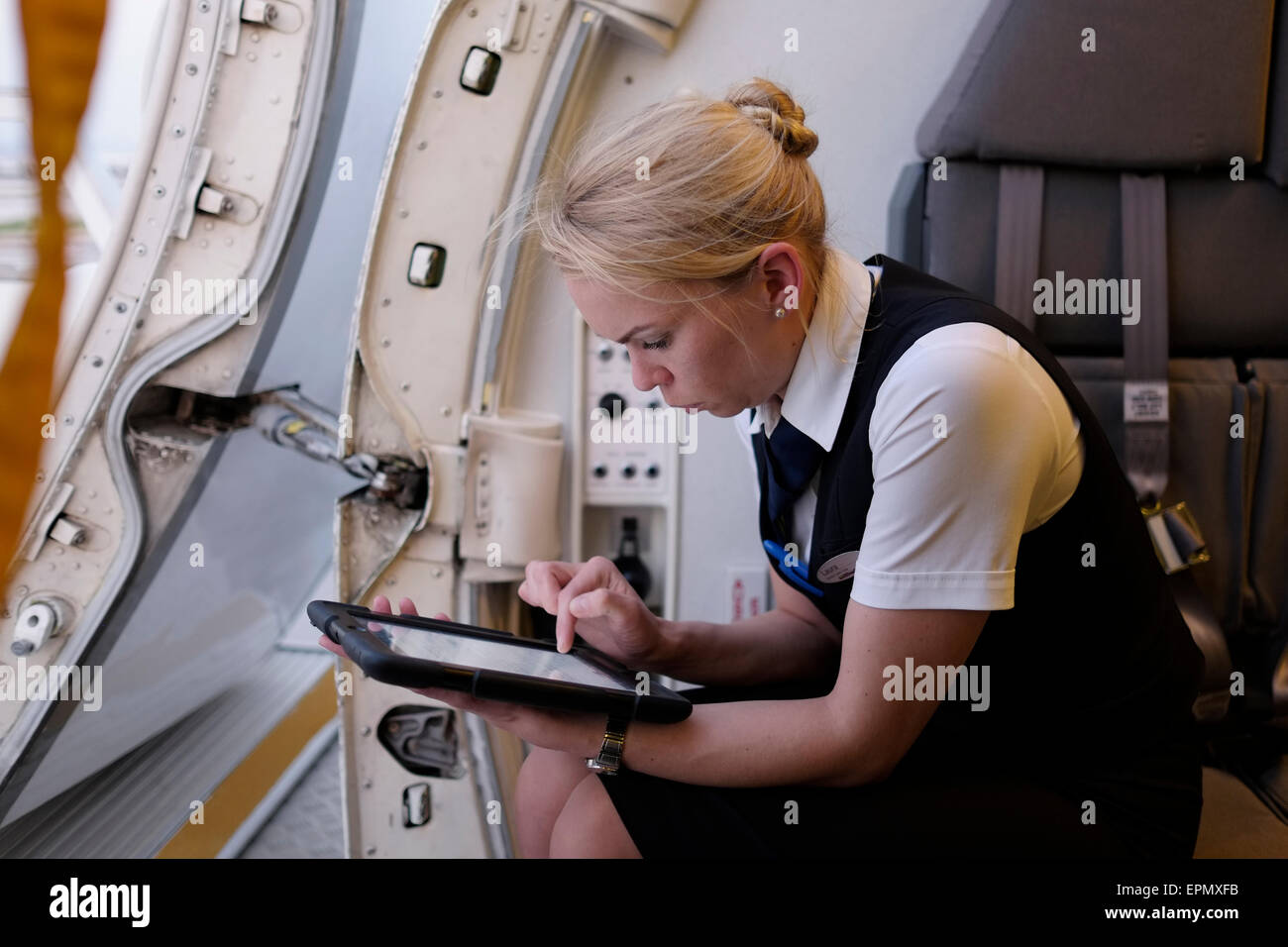 An airplane attendant using a tablet in Air Baltic plane - Stock Image
