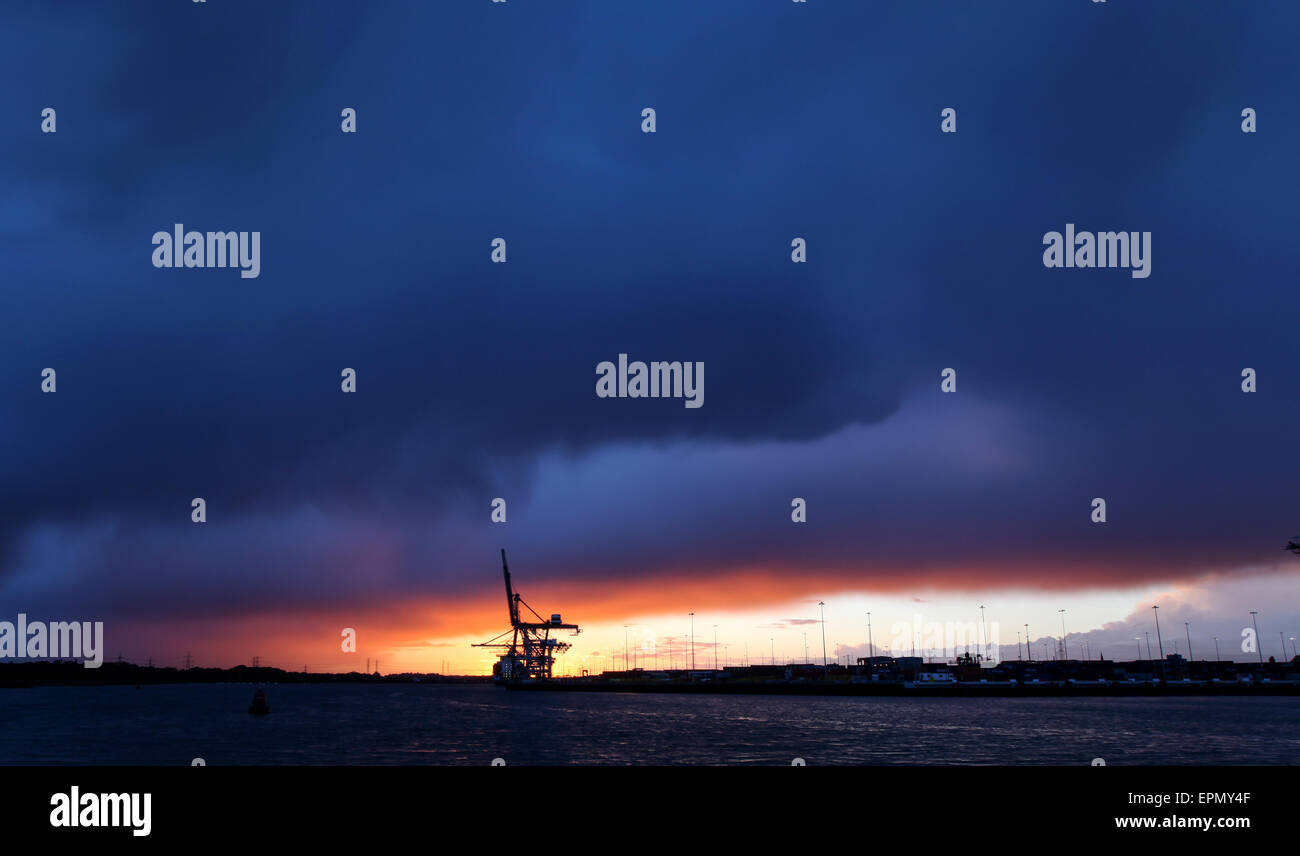 Storm clouds gather over the container port in Southampton Docks as the sun sets - Stock Image