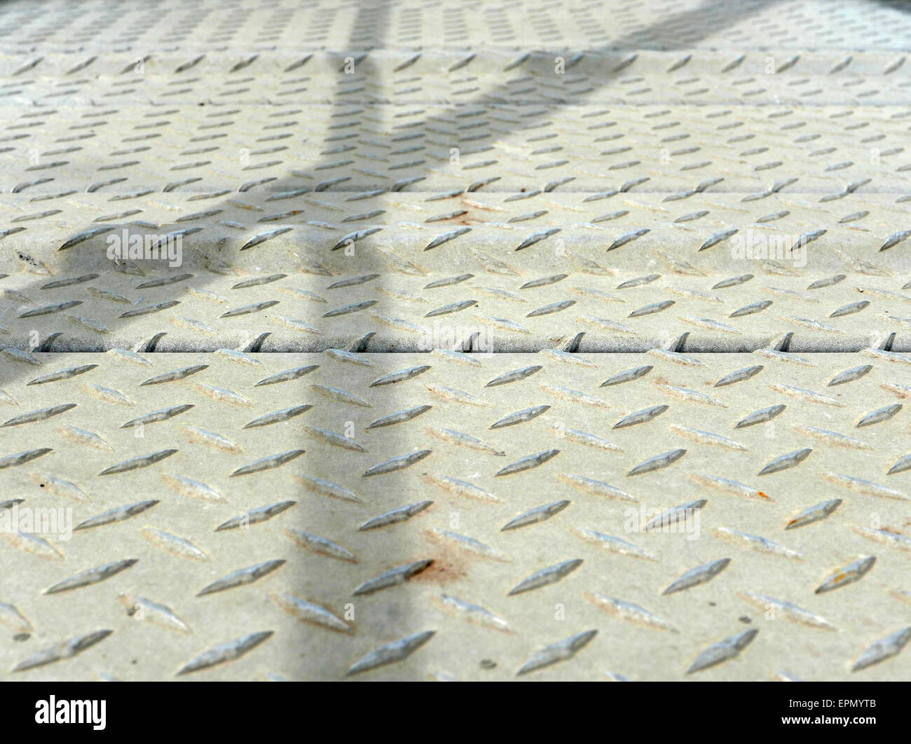 Close view of a steel non-slip walkway with the shadows of the railings. - Stock Image