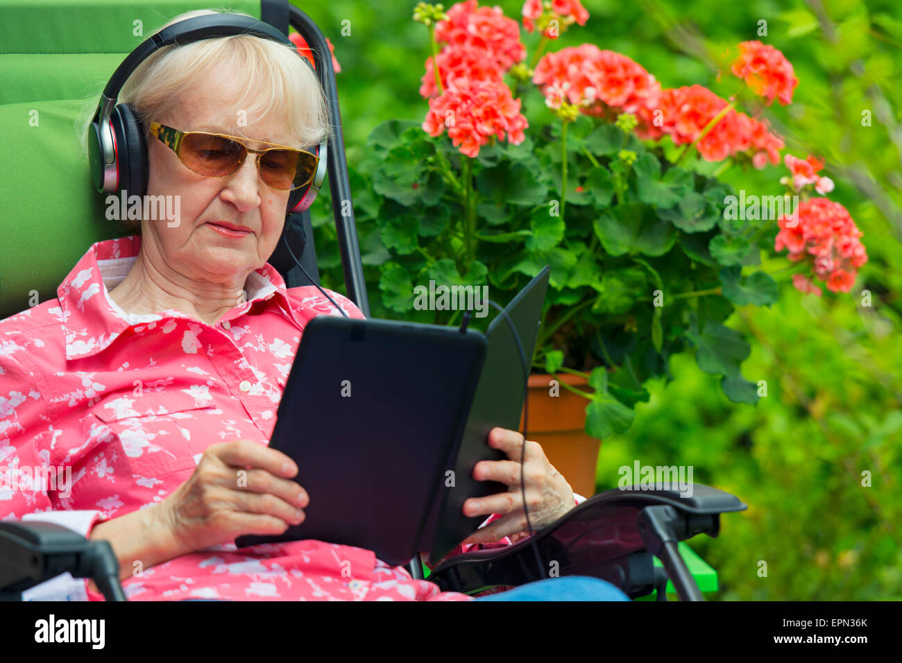Woman with Headphones Reading Listening to Audio Books Content on Tablet or Kindle Device, ebook Reader - Stock Image