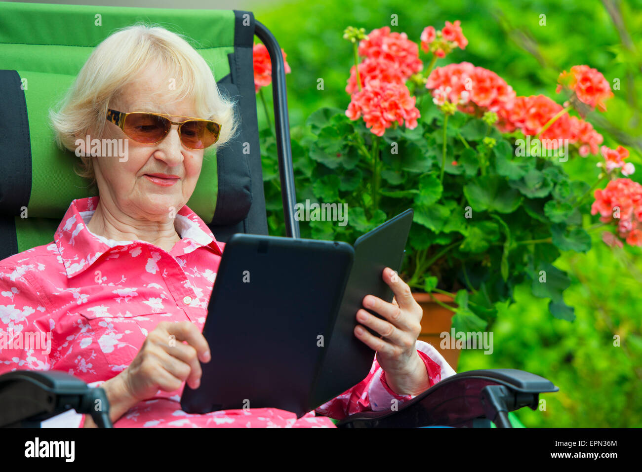 Senior Caucasian Woman reading eBook on Kindle or Tablet - Stock Image