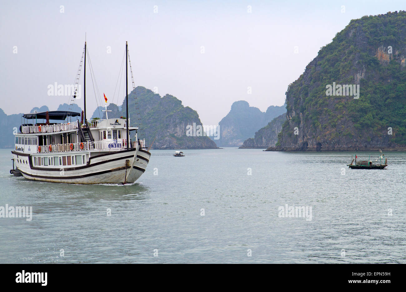 Tourist ship (junk) anf fishing boats in Halong Bay - Stock Image