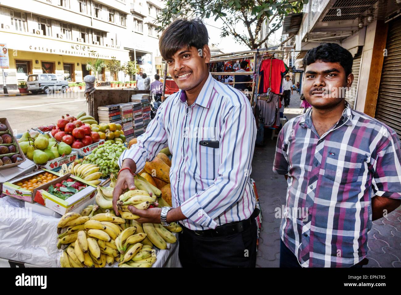 Mumbai India Asian Apollo Bandar Colaba Indumati Sakharkar Marg Causeway Market shopping man sidewalk vendor fruit - Stock Image