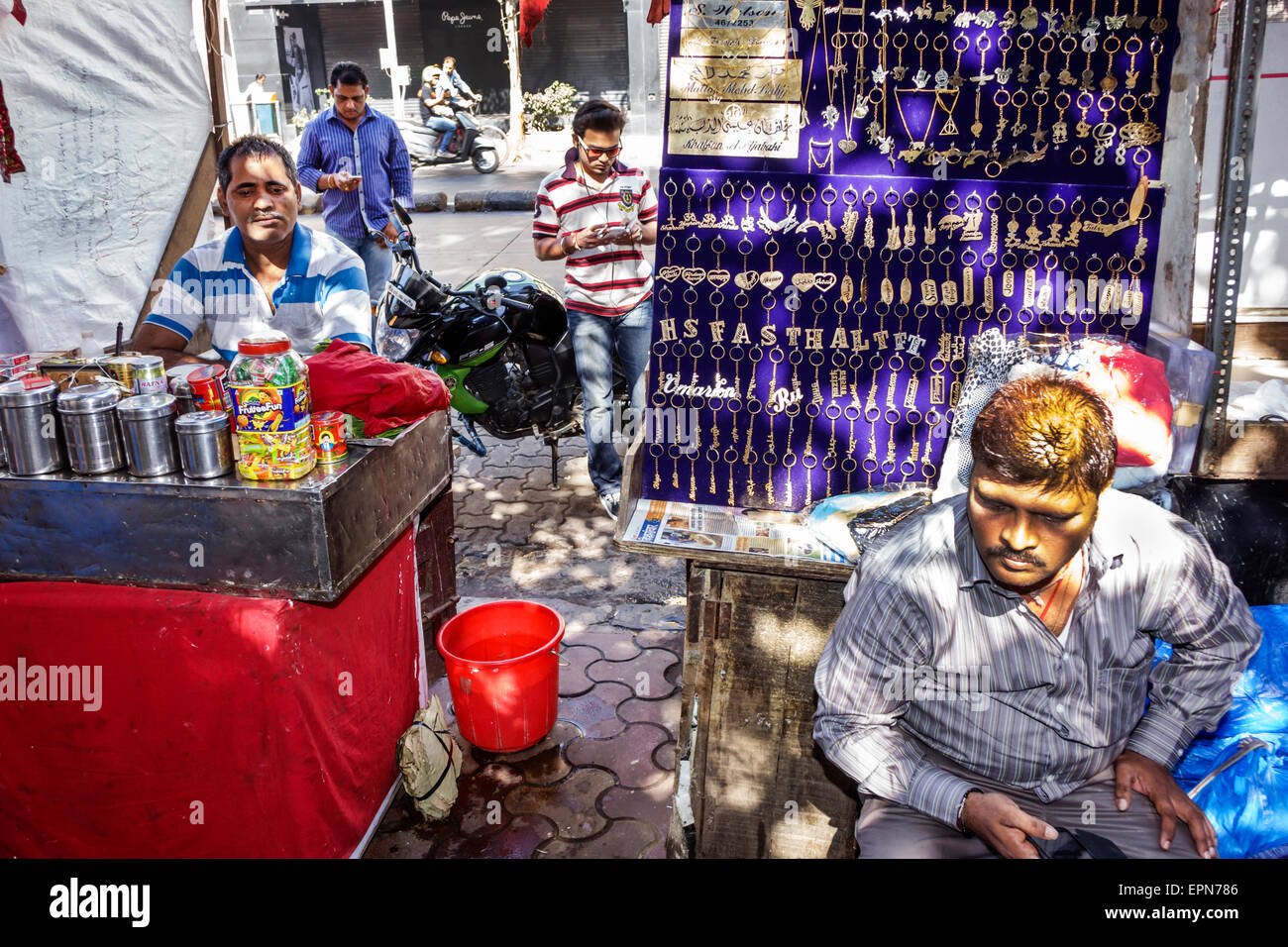 Mumbai India Asian Apollo Bandar Colaba Indumati Sakharkar Marg Causeway Market shopping man sidewalk vendor jewelry - Stock Image