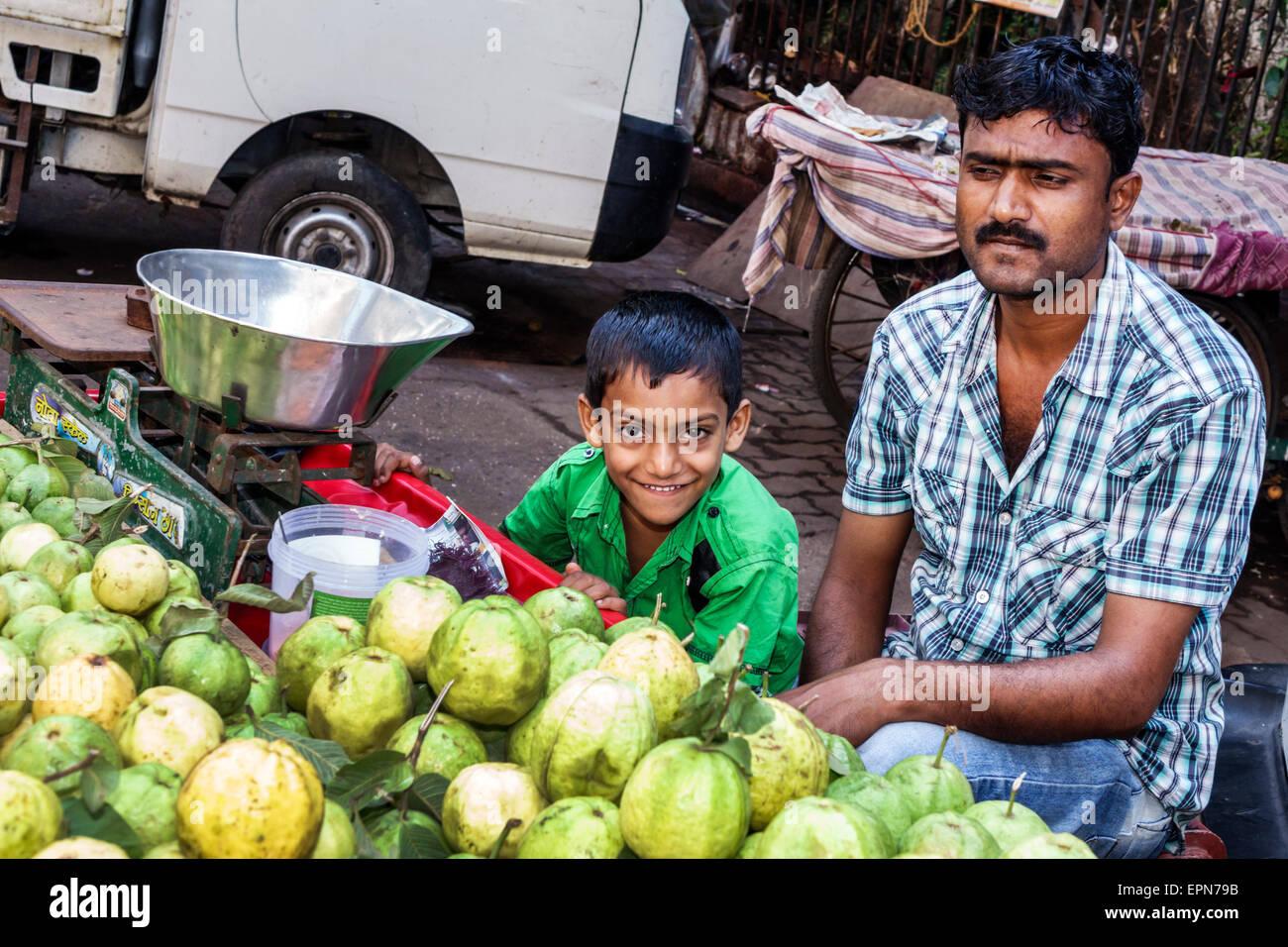 Mumbai India Asian Apollo Bandar Colaba Causeway Market Strand Cinema Road man produce vendor street father boy - Stock Image