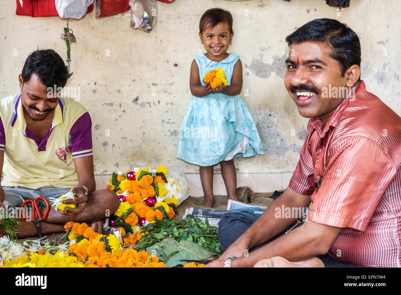 Mumbai India Asian Apollo Bandar Colaba Causeway Market Lala Nigam Road shopping street vendors flower flowers man - Stock Image