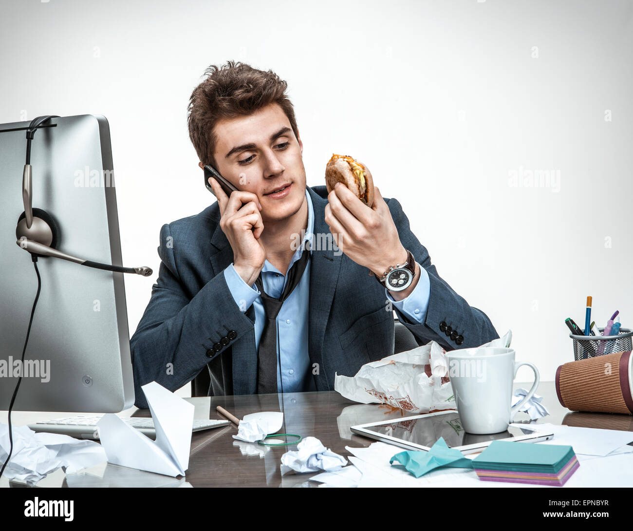 Slacker man talking on the phone while eating at work / modern office man at working place, sloth and laziness concept - Stock Image