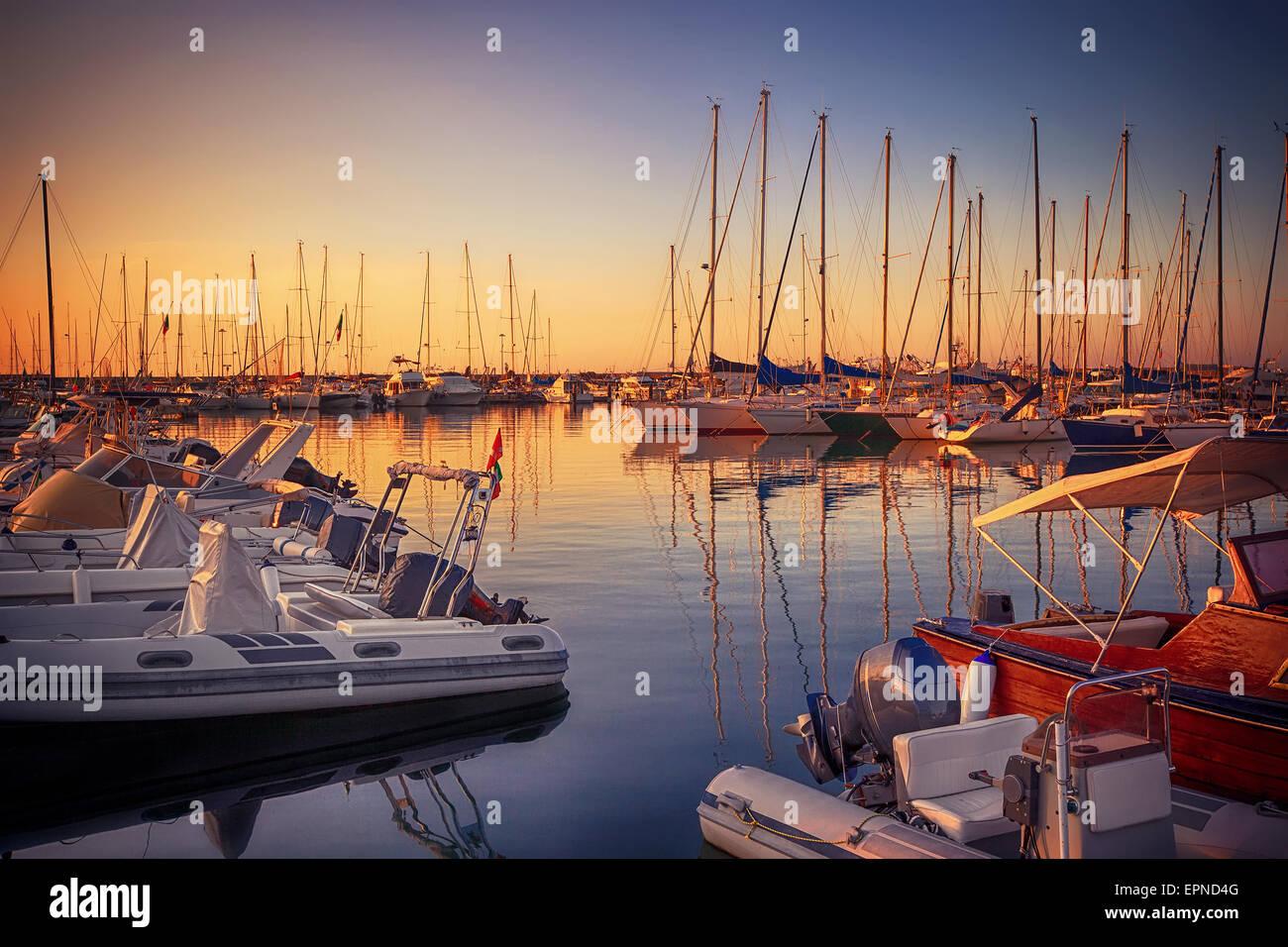 Marina with docked yachts at sunset - Stock Image