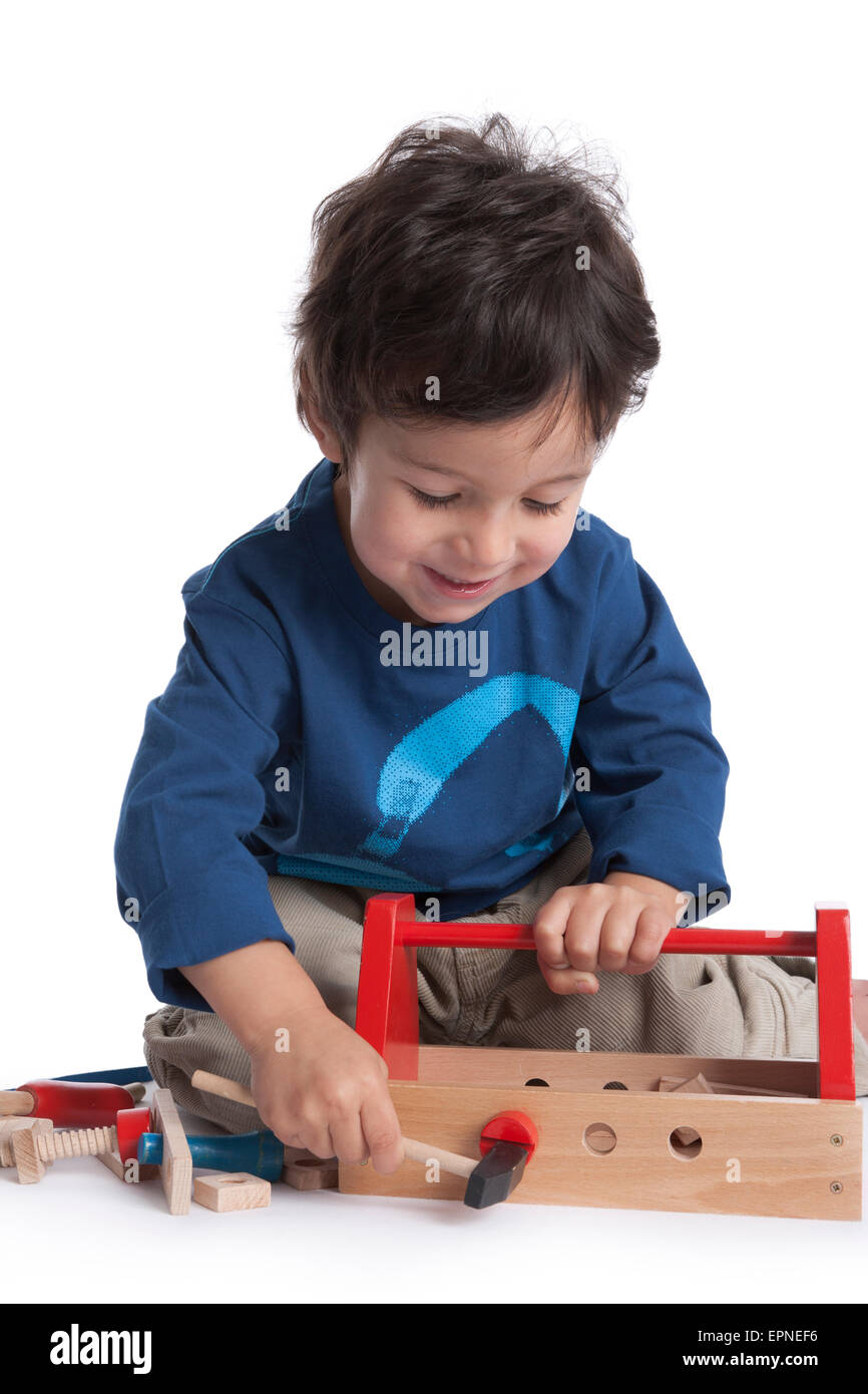 Two year old boy is playing with wooden tools on white background - Stock Image