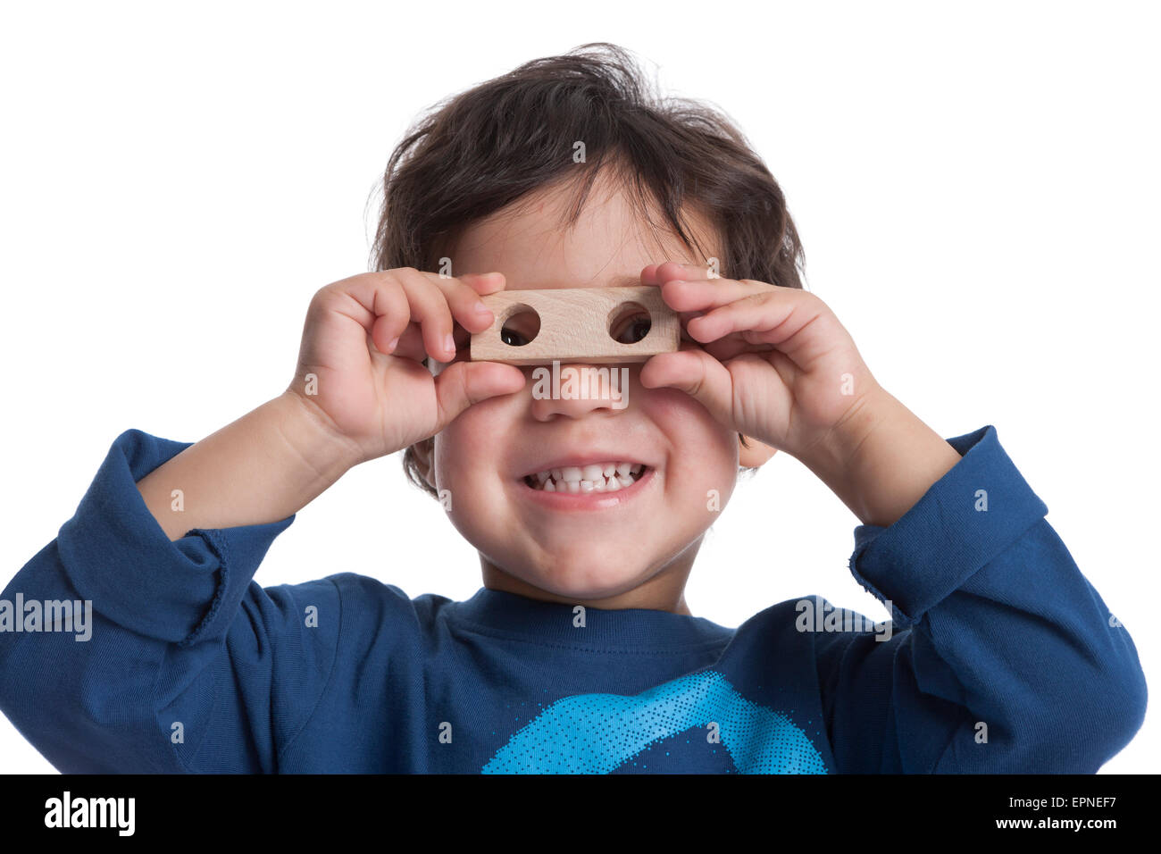 Two year old boy looking through the holes of a block on white background - Stock Image