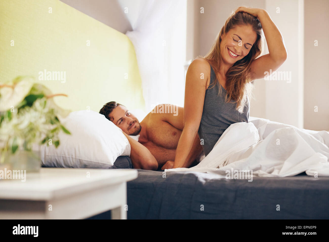 Happy young couple waking up in the morning on bed. Young man and woman smiling, feeling relaxed in morning. - Stock Image
