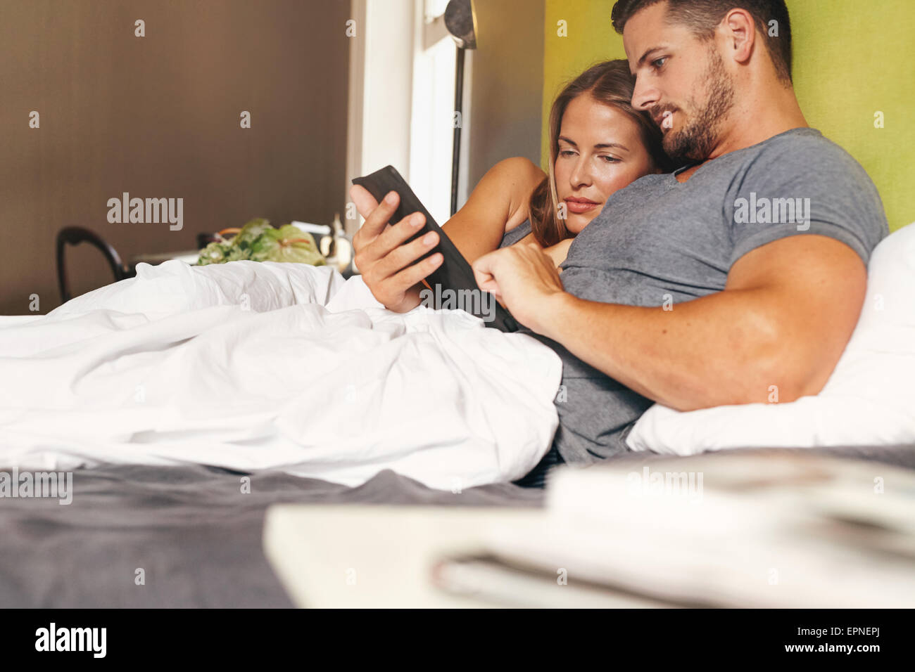 Shot of a young couple lying in bed and using a digital tablet together in morning - Stock Image