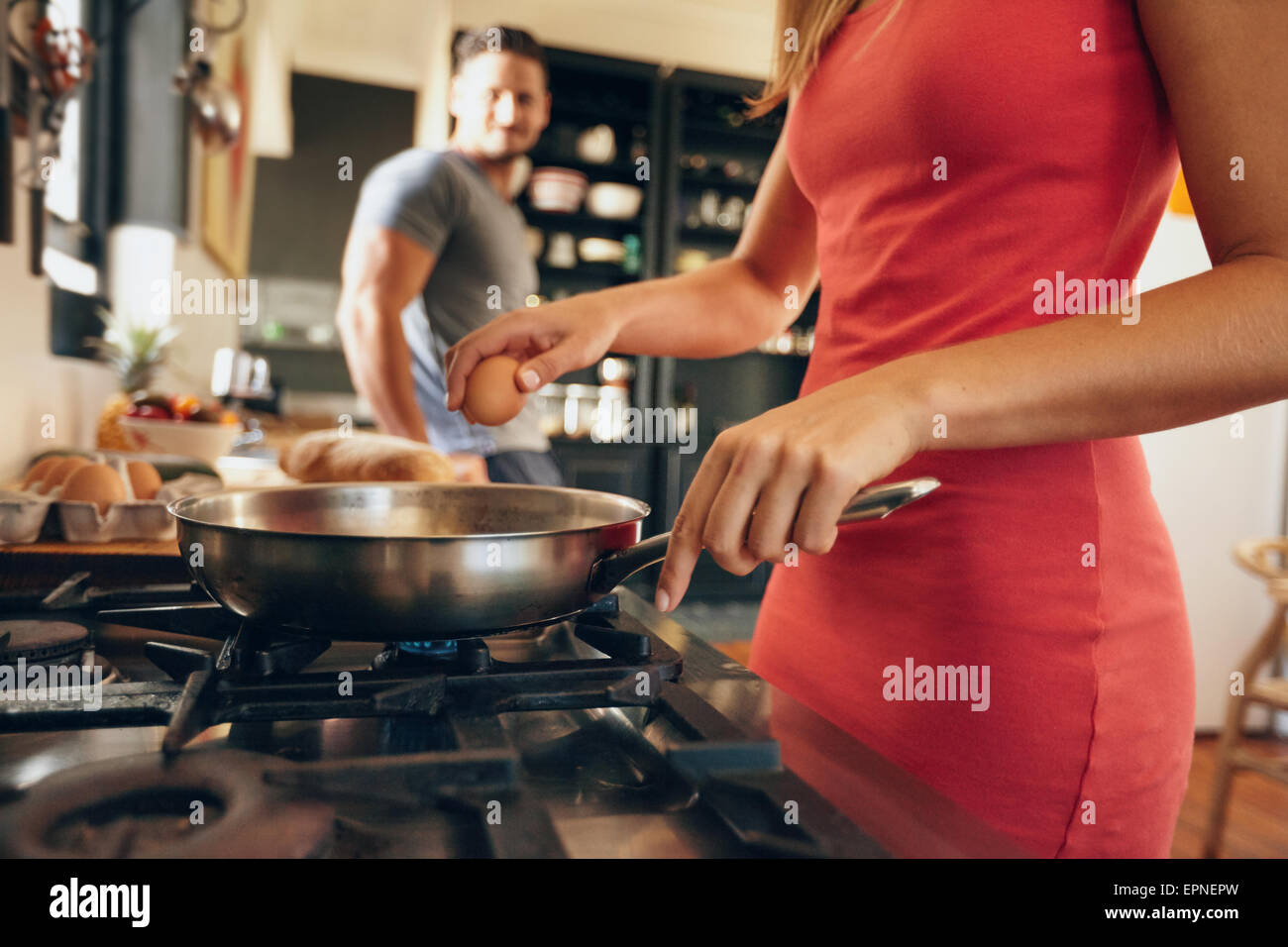 Closeup image of woman cracking an egg into a frying pan with man standing in background in kitchen. Preparing breakfast. - Stock Image