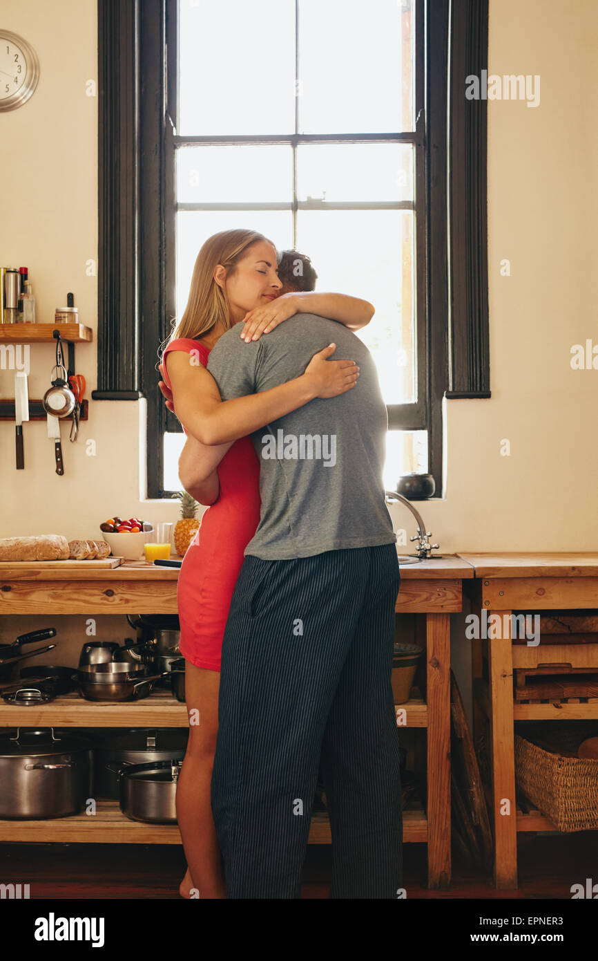 Young couple in love hugging each other. Young man and woman in kitchen embracing. - Stock Image