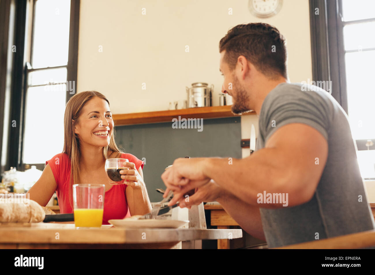 Shot of cheerful young couple having breakfast in kitchen at home. Young woman drinking coffee looking at man smiling - Stock Image